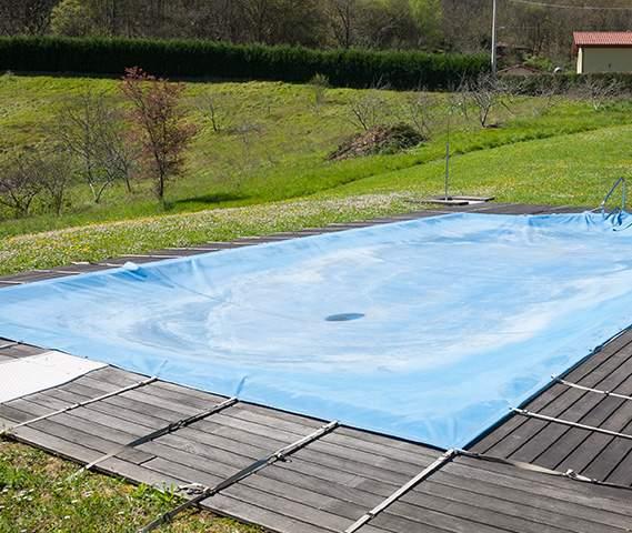 Bâche de loisir posée sur un bassin d'eau vide